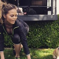 Chrissy Teigens Stretching with her pup